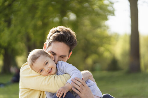 Portrait of happy toddler girl cuddling with her father in a park - DIGF07059