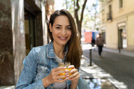 Young woman holding glass with fresh juice - AFVF02960