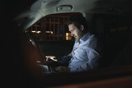 Young man using laptop in car at night - UUF17605