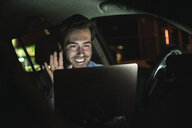 Happy young man having a video conference in car at night - UUF17611