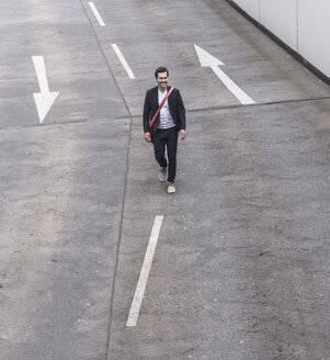 Confident businessman walking on road with arrow signs - UUF17623