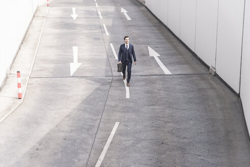Businessman walking on road with arrow signs - UUF17641