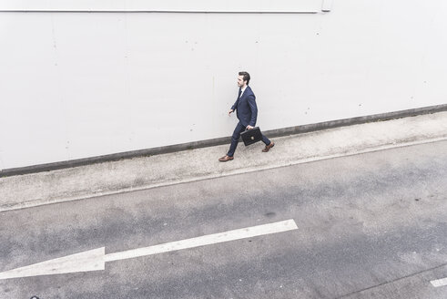 Businessman walking at road with arrow sign - UUF17644
