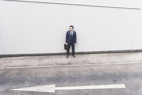Businessman standing at road with arrow sign - UUF17647