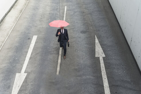 Businessman with umbrella walking on road with arrow signs - UUF17653