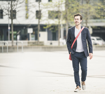 Confident businessman walking in the city - UUF17656