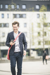 Smiling businessman walking in the city with cell phone and earphones - UUF17662