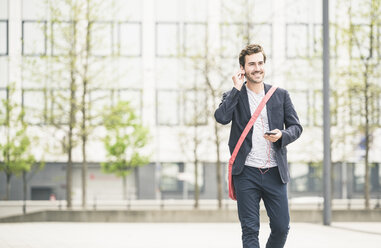 Smiling businessman walking in the city with cell phone and earphones - UUF17665