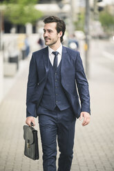Confident businessman walking in the city - UUF17671