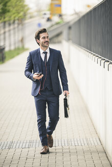 Businessman walking in the city with cell phone and earphones - UUF17674