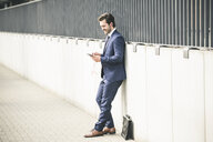 Businessman leaning against a wall in the city checking cell phone - UUF17680