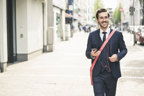 Smiling businessman walking in the city with cell phone and earphones - UUF17683