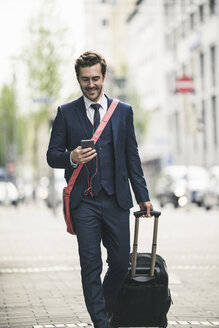 Smiling businessman walking in the city with cell phone and suitcase - UUF17686