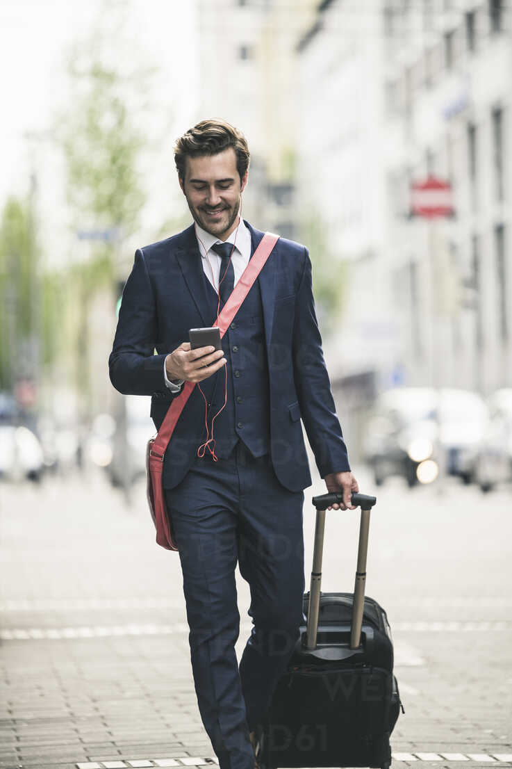 Smiling businessman walking in the city with cell phone and suitcase - UUF17686 - Uwe Umstätter/Westend61