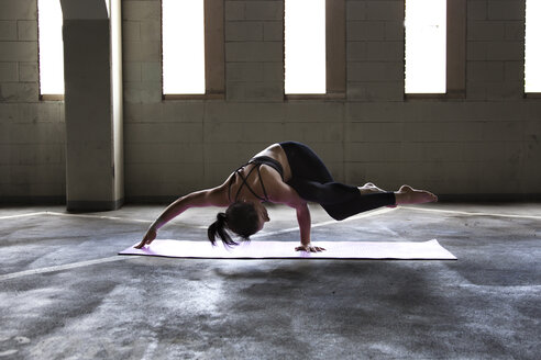 Caucasian woman practicing yoga in parking lot - BLEF03877