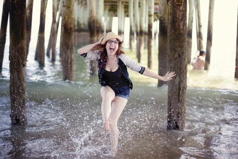 Caucasian woman splashing in ocean under boardwalk - BLEF03922