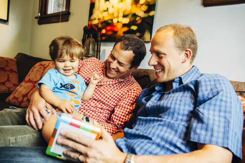 Gay fathers playing with baby son on sofa - BLEF03973