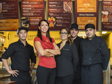 Hispanic business owner and employees smiling in cafe - BLEF04021