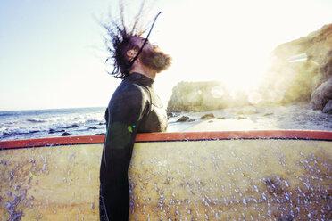 Caucasian man holding surfboard at beach - BLEF04033