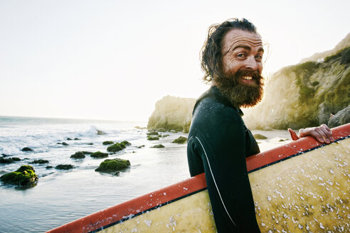 Caucasian man holding surfboard at beach - BLEF04036