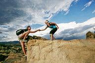 Woman helping friend climb rock formation - BLEF04042