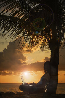 Silhouette of woman with laptop leaning on palm tree - BLEF04057