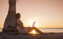Caucasian woman with laptop leaning on palm tree at sunset - BLEF04060