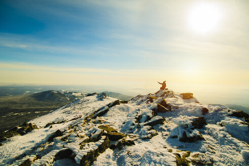 Woman sitting on mountain in winter - BLEF04075