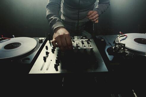 Caucasian disc jockey playing music in nightclub - BLEF04117