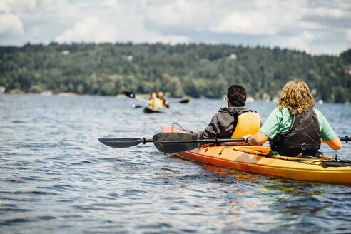 Man and woman holding paddles in kayak - BLEF04147