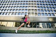 Black woman running and jumping on city sidewalk - BLEF04195