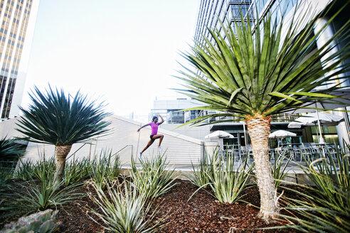 Black woman running and jumping on sidewalk near trees - BLEF04201