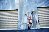 Caucasian woman doing one-handed handstand outdoors - BLEF04270