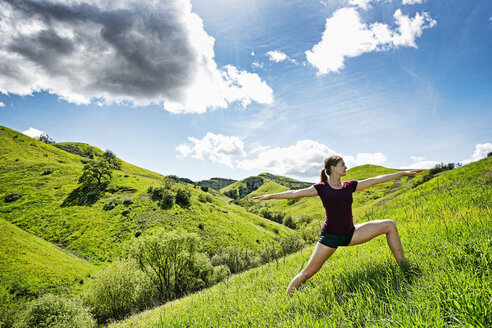 Caucasian woman doing yoga on hill - BLEF04288