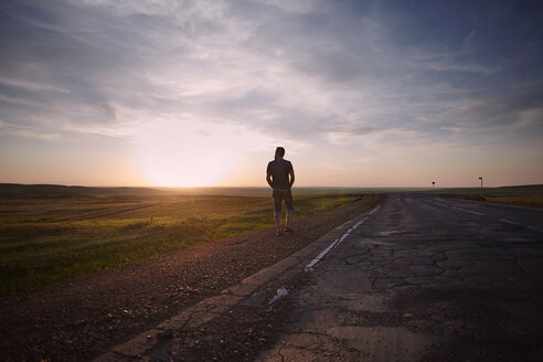Caucasian man standing near cracked road at sunset - BLEF04327