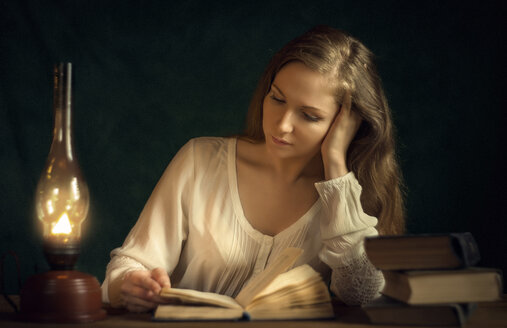 Caucasian woman reading book by candlelight - BLEF04339