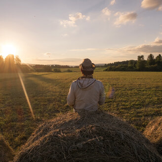 Mari man sitting on hay bale at sunset - BLEF04351