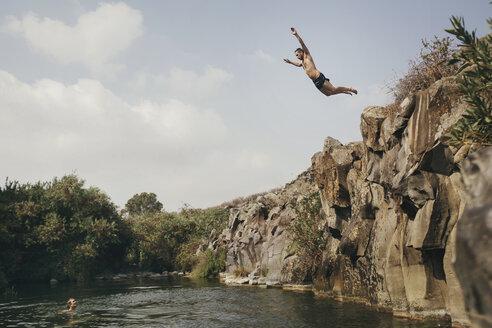 Young man jumping from a cliff, Yehudiya National Park, Israel, Golan, Yehudiya - GCF00253