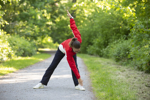 Female mature jogger in the forest, stretching - FLLF00211