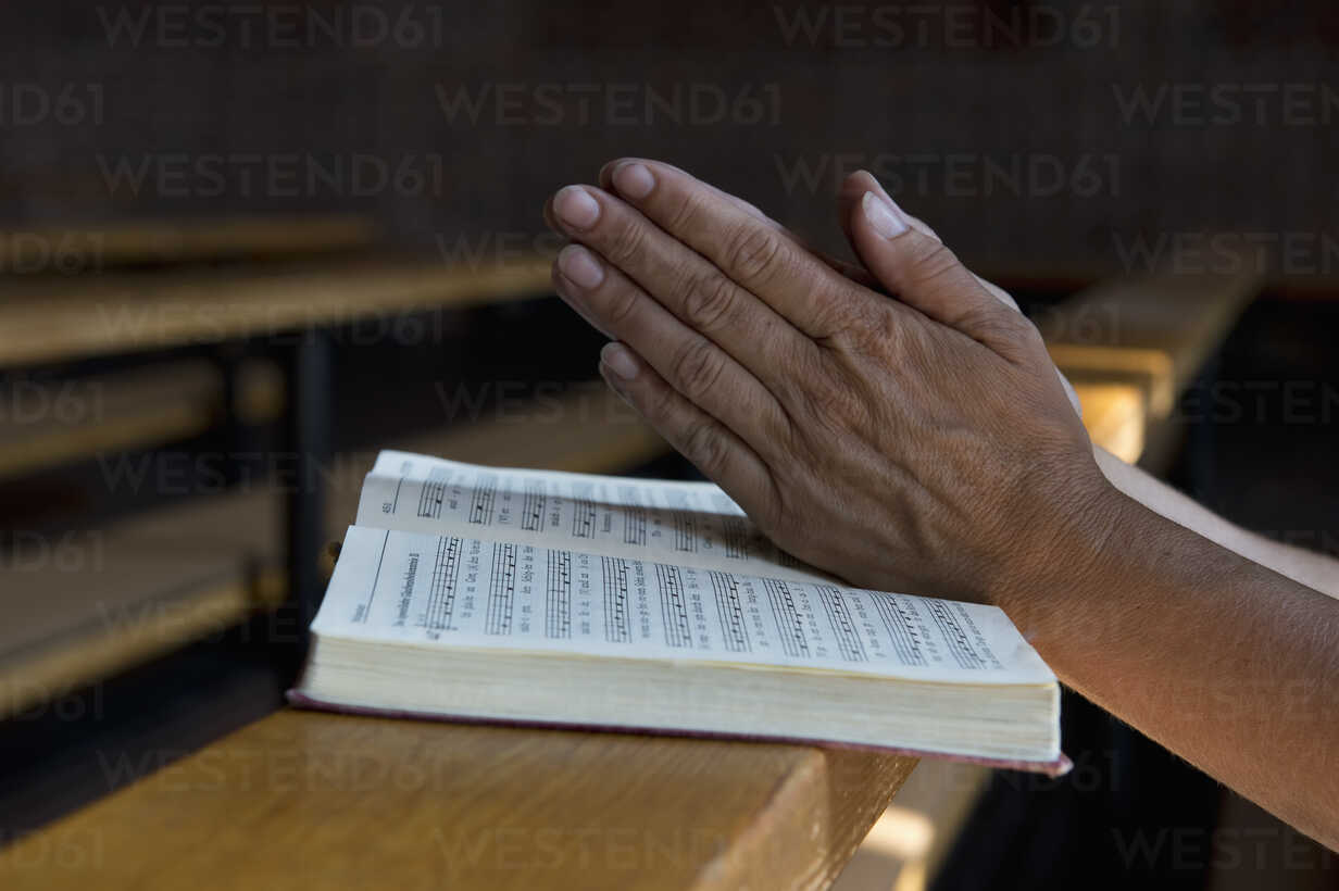 Praying hands on hymnbook on pew - ASF06429 - Achim Sass/Westend61
