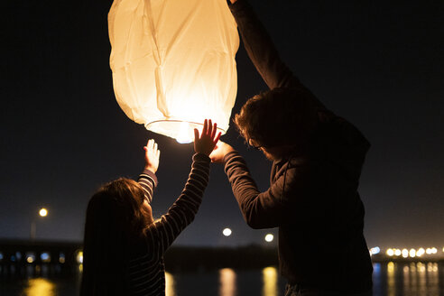 Father and daughter preparing a sky lantern on the beach at night - ERRF01378