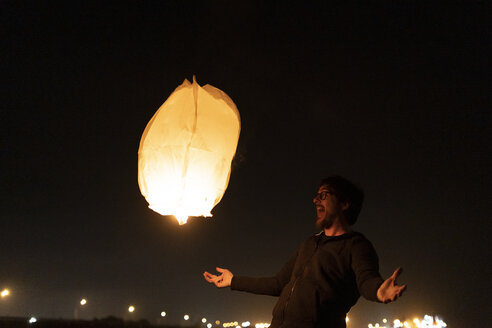 Excited man with floating sky lantern at night - ERRF01381