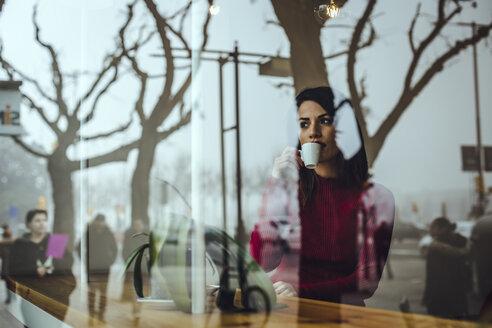 Portrait of a beautiful brunette woman, sitting at window, drinking coffee - ACPF00511