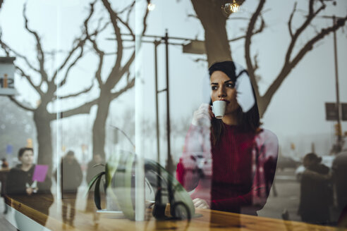 Young woman drinking cup of coffee behind windowpane in a cafe - ACPF00511