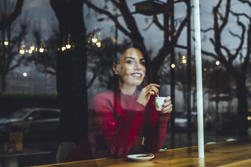 Smiling young woman with cup of coffee behind windowpane in a cafe - ACPF00514