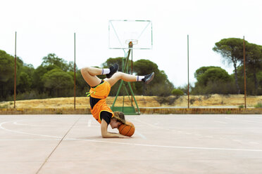 Teenage girl doing acrobatics on basketball ground - ERRF01384