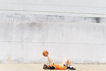 Teenage girl with basketball lying on the ground outdoors - ERRF01387
