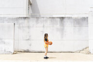 Teenage girl with basketball standing outdoors - ERRF01390
