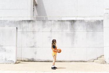 Teenage girl with basketball standing outdoors - ERRF01390