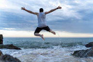 Back view of young man jumping in the air at seafront - AFVF03008